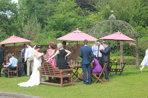 Bride with her wedding guests in the gardens of De Courcey's Manor, Cardiff  Purple themed wedding  Rhiannon & Michael's Real Wedding   Confetti.co.uk