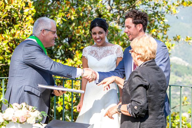 The newlyweds shaking the hands of the registrar |  Outside wedding ceremony ideas | Leanne and Chris's Real Italian Wedding | Confetti.co.uk