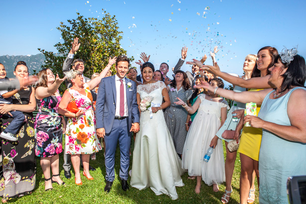 Wedding guests throwing confetti to celebrating the marriage | Outside wedding ceremony ideas | Leanne and Chris's Real Italian Wedding | Confetti.co.uk