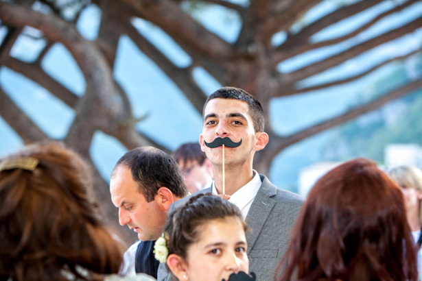 Wedding reception at Villa Maria, Italy Wedding guest holding a comedy moustache| Funny wedding moments to capture | Leanne and Chris's Real Italian Wedding | Confetti.co.uk
