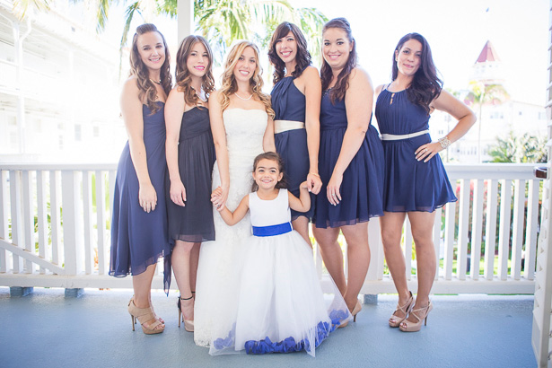 The bride in her strapless lace wedding dress with her bridesmaids in royal blue chiffon short dress and the flower girl in a white and blue dress | Crystal & Giampaolo California Real Wedding |Destination Wedding America | Confetti.co.uk