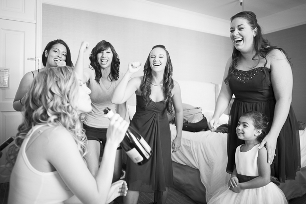 Bridesmaids cheering the bride on as she drinks champagne from the bottle as she gets ready | Crystal & Giampaolo California Real Wedding |Destination Wedding America | Confetti.co.uk