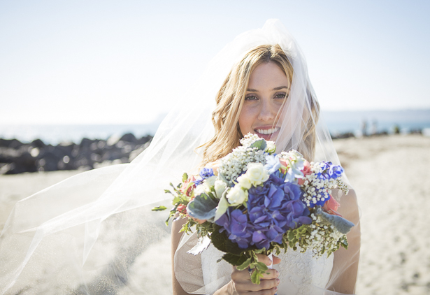 Bride on the California beach holding her rustic wedding bouquet | Crystal & Giampaolo California Real Wedding |Destination Wedding America | Confetti.co.uk