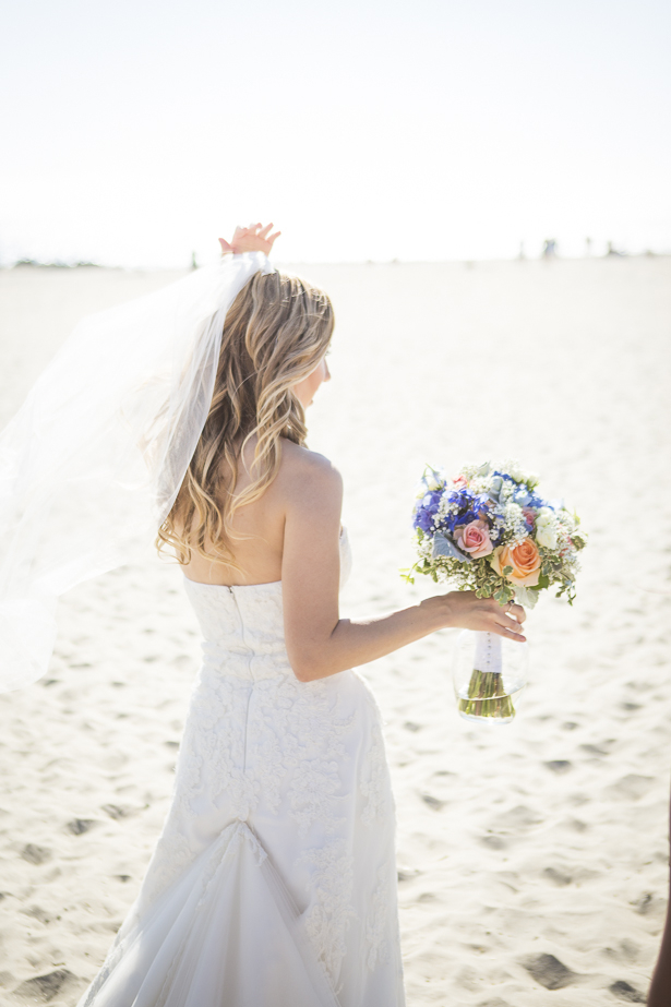 Bride walking on the beach with her bouquet in her hand | Crystal & Giampaolo California Real Wedding |Destination Wedding America | Confetti.co.uk