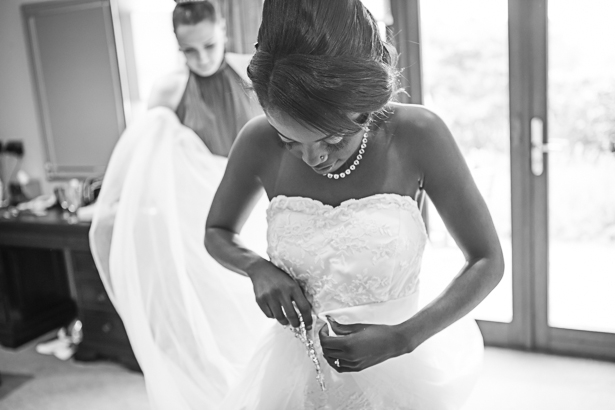 The maid of honour helping the bride with her dress| Wedding moments to capture | Precious and Jerald's real wedding | Confetti.co.uk