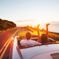 Honeymooners driving towards a beautiful sunset