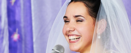 Bride holding a microphone, making a bride's speech