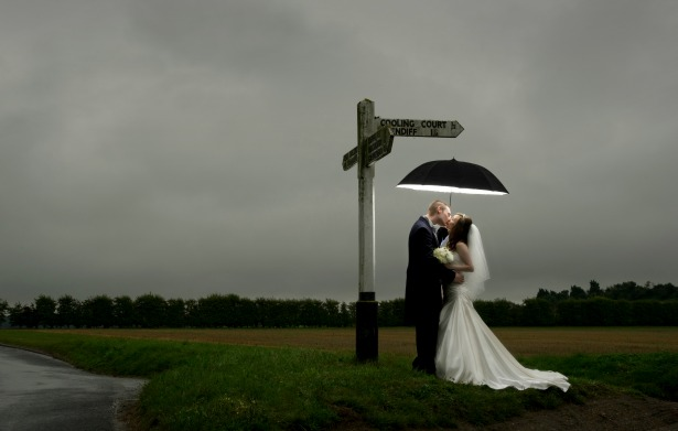 Evening wedding bride and groom kissing in the rain under umbrella by Fabulous Wedding Photography | Confetti.co.uk