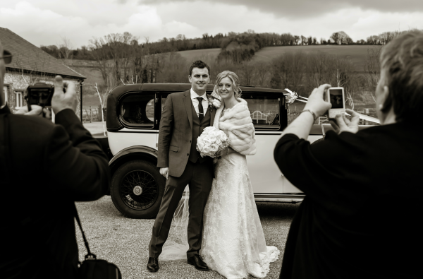 Bride And Groom Pose In Front Of Their Wedding Car | Confetti.co.uk