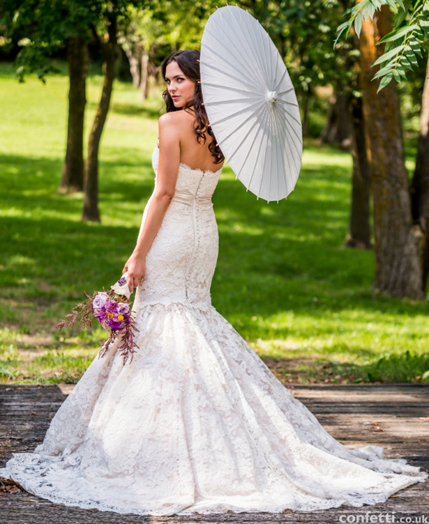 Girl posing with beautiful wedding gown and flowers and stunning parasol from the Confetti Shop