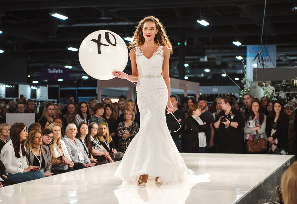 Bride holding a giant balloon on the National Wedding Show Catwalk