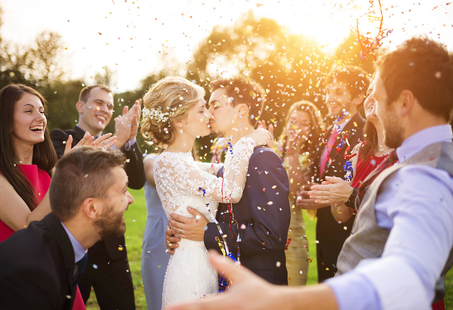 Kissing Bride and Groom in Confetti with Clapping Guests   Confetti.co.uk