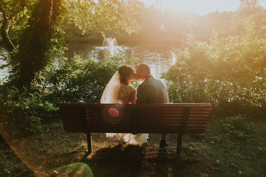 Kissing Bride and Groom on a Park Bench by a Lake and Fountain with Shining Sunlight   Confetti.co.uk