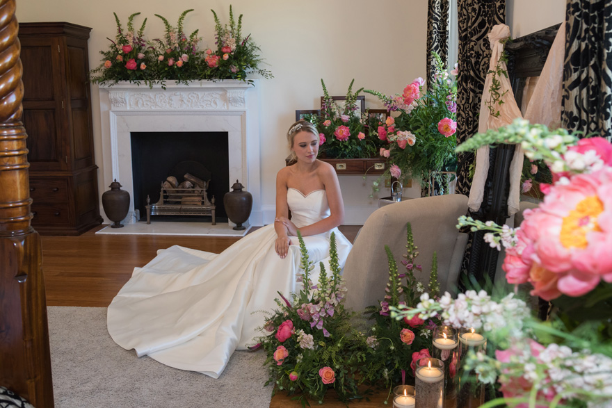 Bride Sitting by a Fireplace in a Bridal Dressing Room - Bride Surrounded by Summer Flowers | Confetti.co.uk