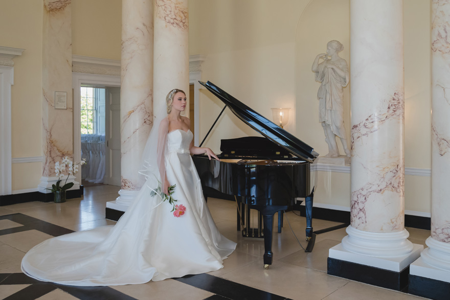 Bride Standing by a Grand Piano - Bride Wearing a Ball Gown and Holding a Flower - Marble Function Room | Confetti.co.uk