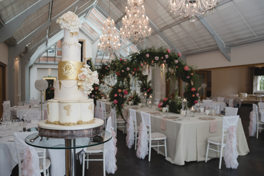 Lavish White and Gold Cake by Unique Cakes by Yevnig - Ornate Tiered Wedding Cake at Botley's Manor Wedding Reception | Confetti.co.uk