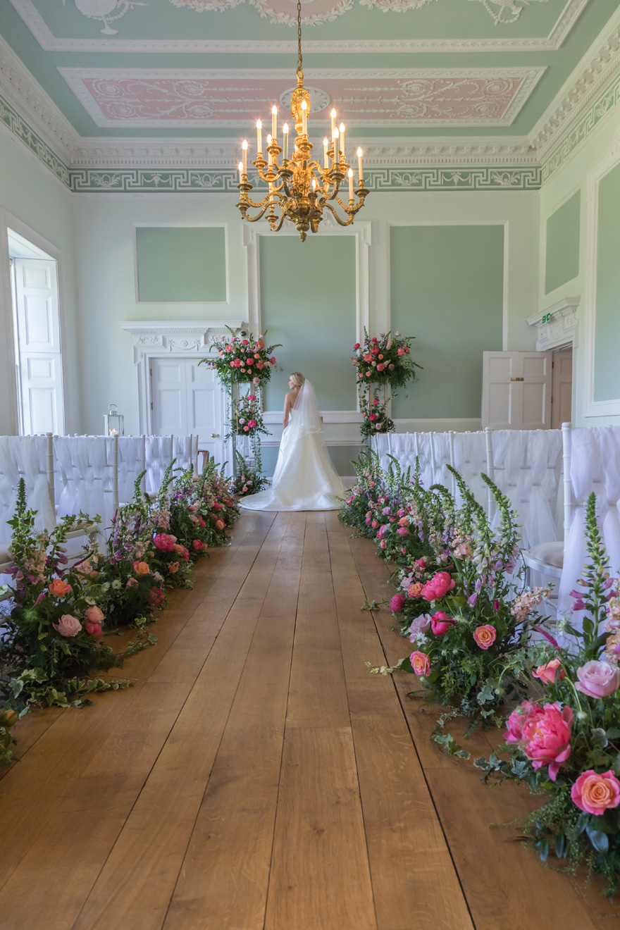 Pink Flowers Wedding Aisle with Golden Chandelier - Beautiful Wedding Aisle Decor - Wedding Aisle Inspiration - Botleys Mansion Wedding Ceremony - Flowers Lining the Aisle | Confetti.co.uk