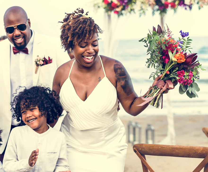Black Bride with Tattoo - Colourful Beach Wedding - Brides with Tattoos - Happy Bride and Groom in a Wedding Ceremony at a Tropical Island by Rawpixel on Shutterstock | Confetti.co.uk