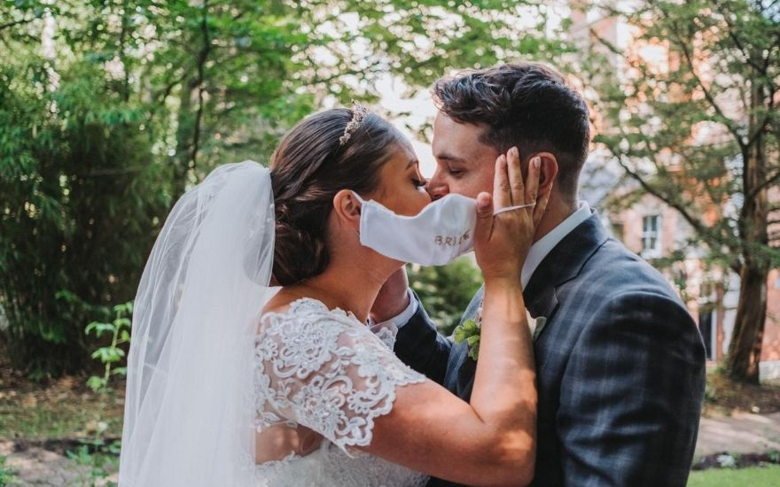 Bride and groom kissing behind face mask