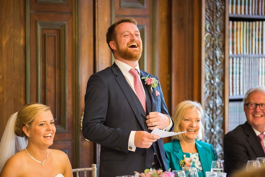 Groom laughing whilst reading a groom's speech